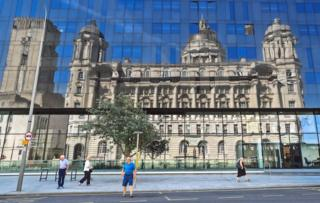 A reflection of the Port of Liverpool Building under blue skies seen in a glass building