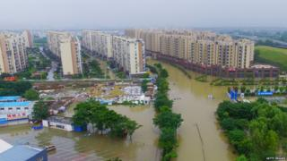 Blocks of flat surrounded by muddy flood water