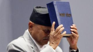 Nepalese President Ram Baran Yadav displays the constitution, formally adopted following a decade of political infighting, in Kathmandu, Nepal, Sunday, Sept. 20, 2015.