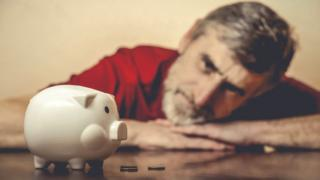 man looks at piggy bank