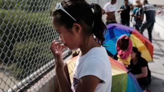 A Honduran girl waits with her family along the border bridge after being denied entry from Mexico into the US