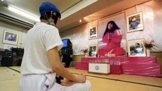 Follower meditating in front of portraits of Aum Supreme Truth guru Shoko Asahara (1999)