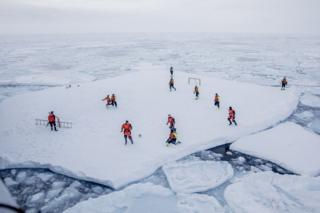 People play football on a large flat piece of ice in the sea