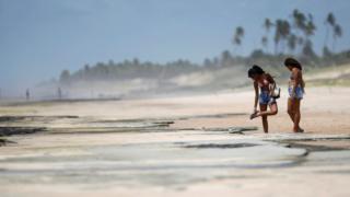 Duas banhistas na areia manchada de óleo, uma delas olhando para a sola do chinelo