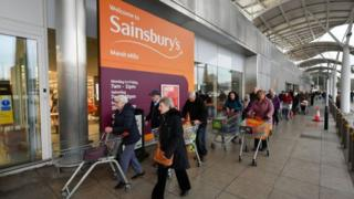 Customers queuing outside Sainsburys