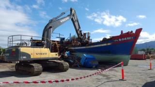 The blue, wooden Vietnamese boat, being destroyed at a court in Cairns