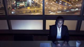 Mulher digita em computador dentro de escritório, com vista da cidade grande à noite na janela