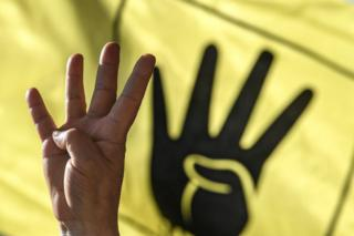 A man's hand is seen gesturing with four fingers held up. A black-and-yellow banner behind him depicts a hand making an identical gesture.