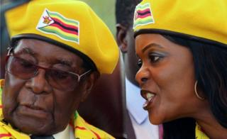 President Robert Mugabe listens to his wife Grace Mugabe at a rally of his ruling ZANU-PF party in Harare, Zimbabwe, November 8, 2017