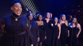A choir performing at AEW Revolution