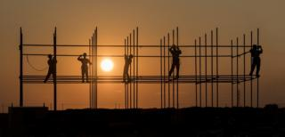 Workers working on scaffolding during sunset