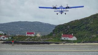 Loganair flight taking off from the runway on Barra beach
