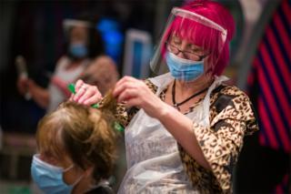 A hairdresser cuts a customer's hair