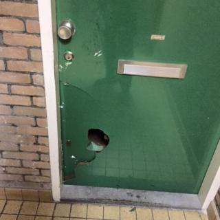 a green door with a hole kicked into it