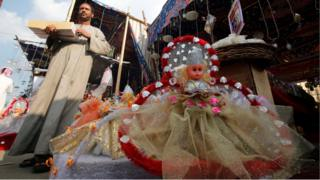 """A vendor selling traditional sweets and """"Aroset El Moulid"""" (Bride of Moulid) dolls waits for customers at a market ahead of the religious holiday of Mawlid al-Nabi, the birthday of Prophet Mohammad, in Old Cairo, Egypt December 8, 2016"""
