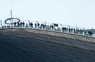 Visitors looking at the view from the skypark of the 55-storey hotel tower of Marina Bay Sands in Singapore, 26 August 2010