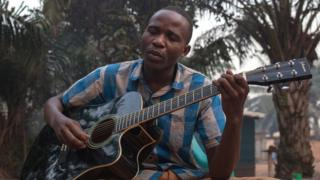 Emmanuel Ngallos sings one of his own compositions while sitting in the front yard of his family home in the Sango neighbourhood of Bangui.