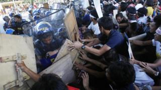 警官隊と押し合うデモ参加者(19日、マニラ)