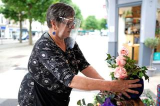 A woman puts out flowers on a stall whilst wearing a face shield