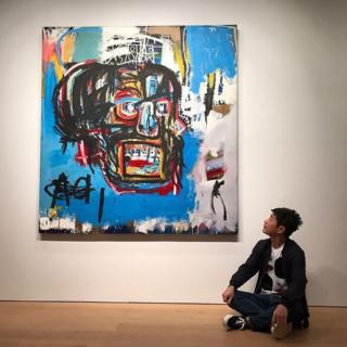 Yusaku Maezawa sitting cross-legged next to the Basquiat painting