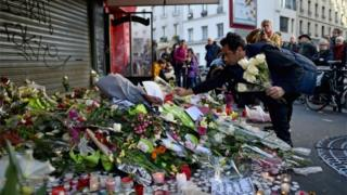 A man places a flower outside of the La Belle Equipe restaurant on Rue de Charonne following Friday's terrorist attack