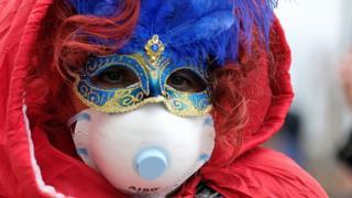 Un asistente al carnaval de Venecia usando una mascarilla protectora junto a su disfraz.