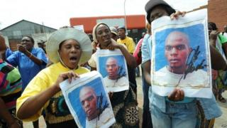 Protesters hold on 8 March 2013 portraits of Mido Macia, a Mozambican taxi driver, outside the Benoni court where police officers charged with murdering him appeared.