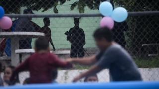 Children playing on a concrete court, while armed youths watch on
