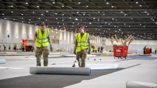A hand-out picture provided by the British Ministry of Defence showing soldiers from 1 Royal Anglian Regiment as they assist with building the Nightingale Hospital at the ExCel conference centre in London