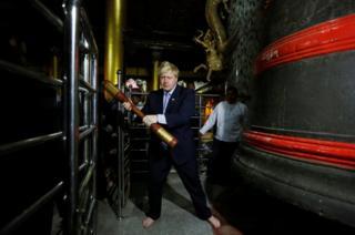 British Foreign Secretary Boris Johnson hits a bell while visiting Shwedagon Pagoda in Yangon, Myanmar