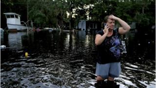 Lynne Garrett habla por teléfono con el agua a la altura de la rodilla tras el paso del huracán Hermine por Tampa, Florida, el 2 de septiembre.