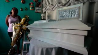 Karina Navarrete stands next to the coffin of her fifteen-month-old son Teiler Lorio Navarrete