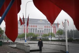 A North Korean man walks out of an underpass while seen framed by the Workers' Party flags, in front of the April 25 House of Culture, the venue for the 7th Congress of the Workers' Party of Korea on Friday, 6 May 2016, in Pyongyang, North Korea.