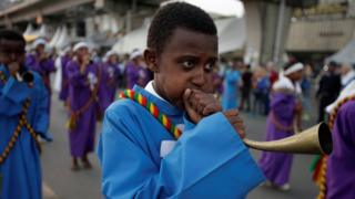 One choir member dey blow local trumpet for di Meskel Festival.