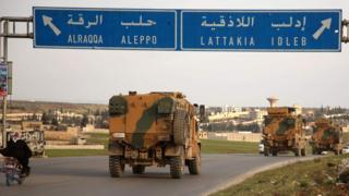 Turkish military vehicles drive past the town of Atareb, Syria, as they head towards Idlib province (3 February 2020)