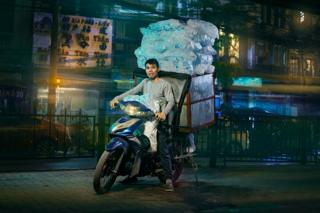 a man posed on his motorcycle, carries an astonishing amount of ice in a box rigged to the vehicle