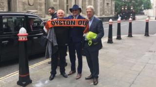 "Owen Oyston (centre) poses outside the court holding a protester's ""Oyston Out"" Blackpool scarf"