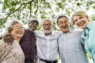 five elderly people hug and smile