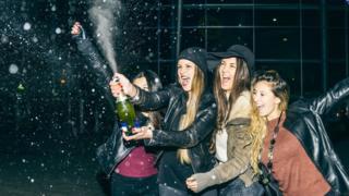 Cuatro mujeres descorchando una botella de champagne.