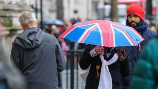 A woman shelters from the rain beneath a Union Jack umbrella during rainfall in central London.