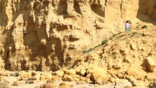 A child climbing on a collapsed section of cliff