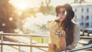 A glamorous woman smoking an e-cigarette