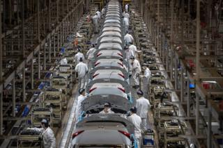 People wearing protective face masks work on an assembly line at the Dongfeng Honda plant in Wuhan