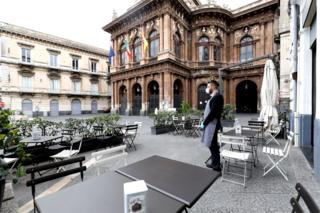 A waiter wearing a face mask stands outside a deserted restaurant