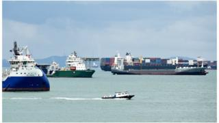 A boat sails past shipping vessels anchored off at the straits in Singapore on 11 August 2014.