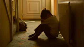 Boy sitting against a radiator in a hallway with his head down