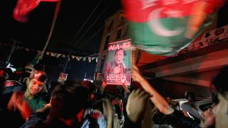 Supporters of Imran Khan, chairman of the Pakistan Tehreek-e-Insaf political party, celebrate near his residence in Bani Gala during the general election, in Islamabad