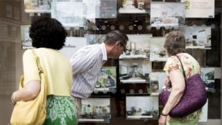 People looking in the window of an estate agent