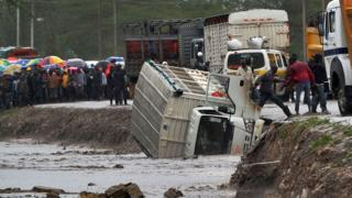 A man is assisted to climb off a truck that was washed off a road by flash floods at Isinya some 58kms south-east of Nairobi on March 15, 2018.