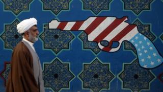 رجل دين إيراني يمشي إلى جوار جدارية على حائط لمقر السفارة الأمريكية سابقا